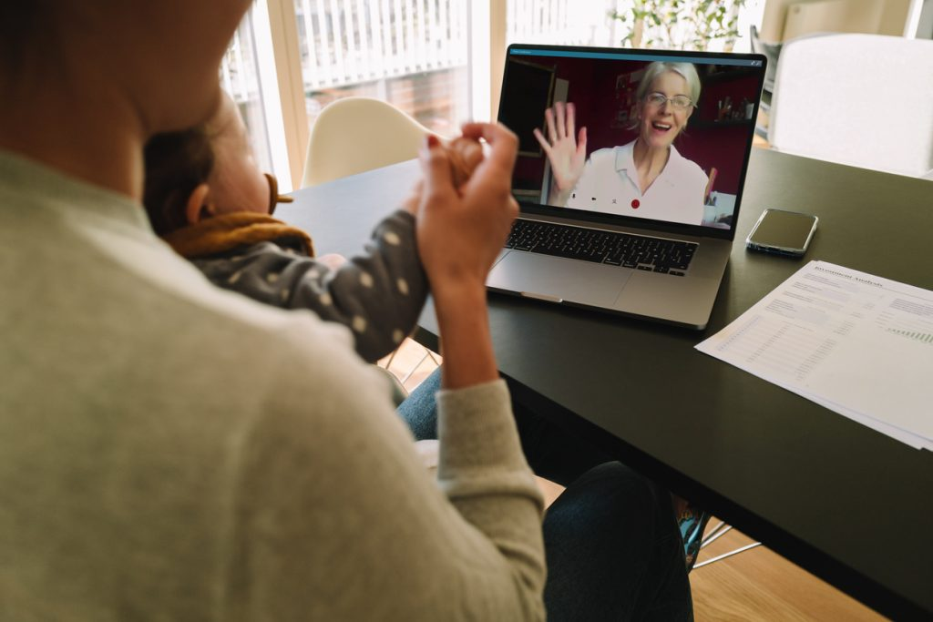 Woman with her daughter having video call with her mother. Woman connecting with her mother on a video call while at home.
